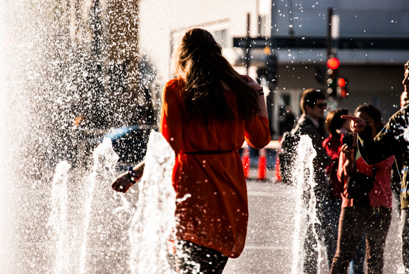 Girl playing in the Place des Festival fountains