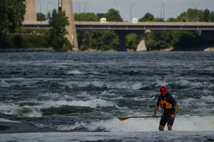 Paddle boarder riding rapids at Habitat 67